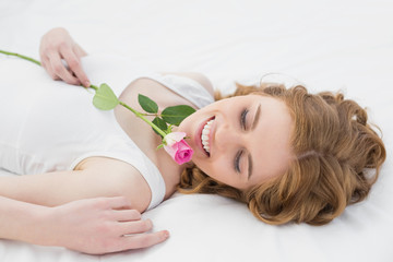 Pretty relaxed woman resting in bed with rose