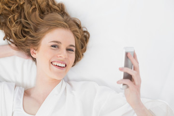 Relaxed young blond with mobile phone in bed