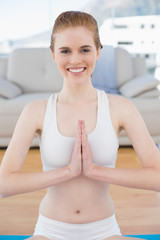 Toned woman in Namaste position at fitness studio