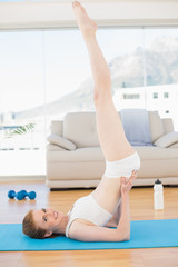 Sporty young woman stretching body in fitness center