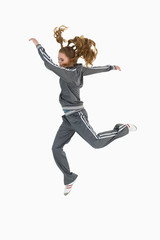 Full length side view of a sporty young blond jumping