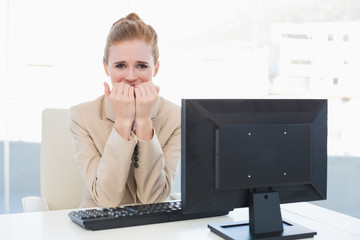 Worried businesswoman biting nails at desk in office