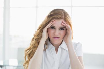 Elegant businesswoman suffering from headache in office