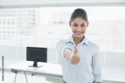 Smiling businesswoman gesturing thumbs up at office