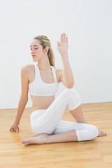 Concentrated young woman stretching her body sitting in sports h