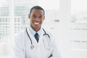 Confident smiling male doctor in a medical office