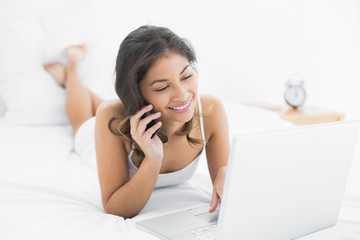 Woman using laptop and cellphone in bed