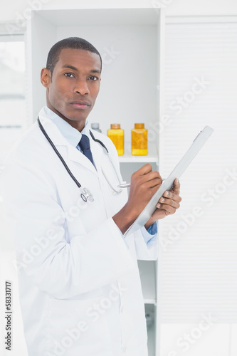 Serious doctor writing a prescription in medical office