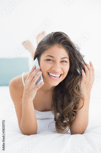 Cheerful woman using mobile phone in bed