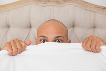 Shocked bald man covering face with sheet in bed
