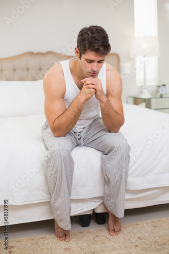 Full length of thoughtful man sitting in bed