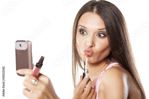 girl applied lipgloss to her lips and use a phone as a mirror