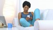 African American woman using mobile phone on couch