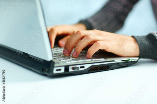 Closeup image of a male hands typing on laptop keyboard