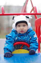 baby in baby car on playgroud outdoors