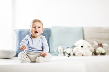 Adorable laughing baby boy sitting on sofa and looking up.