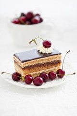 Portion of Opera cake decorated with fresh cherry