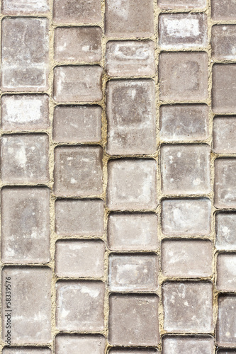 Path background fragment. Path made of small grey bricks.