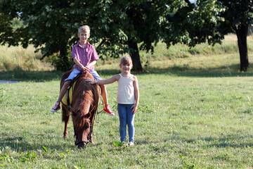 boy and little girl with pony horse pet