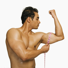 Close-up of a man measuring his biceps with a tape measure