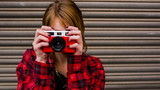 Teenage hipster woman having fun taking pictures with old camera