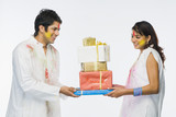 Couple holding Holi gifts