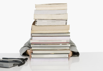 Business person hiding behind a stack of books