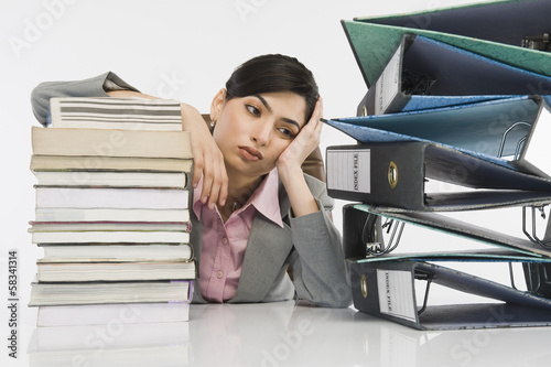 Stack of books in front of a businesswoman at desk