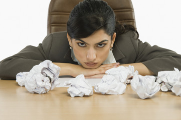 Businesswoman staring crumpled papers on her desk