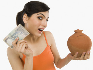 Woman holding Indian currency notes with a piggy bank