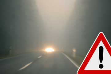 Bad weather driving - foggy road with traffic sign
