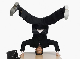 Businessman doing headstand on a conference table