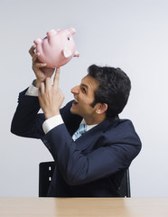 Businessman looking angry while emptying a piggy bank