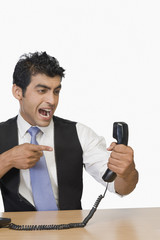 Businessman shouting at a telephone receiver