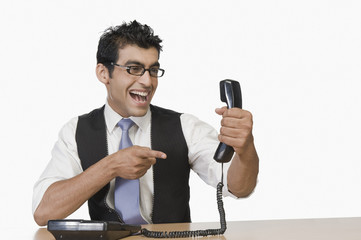Businessman pointing at a telephone receiver and smiling