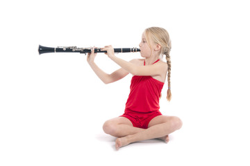 young sitting girl in red playing clarinet