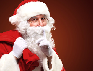 Santa Claus carrying red sack and showing gesture of silence