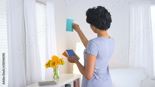 Black woman looking through paint chips