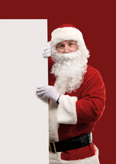 Santa Claus looking out from behind the blank sign isolated