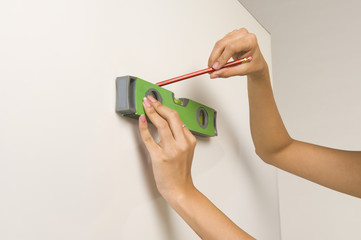 Woman using a spirit level and marking on the wall