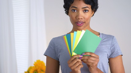 African American woman holding up fan of paint chips
