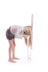 young girl in silver jacket having fun with  trombone