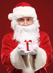 kind Santa Claus giving xmas present and looking at camera
