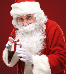 happy Santa Claus looking into white giftbox in isolation