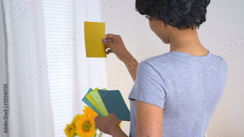 Black woman using paint chips to pick out color for room