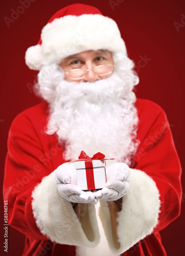 kind Santa Claus giving xmas present and looking at camera