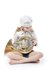 sitting young girl with cap playing french horn