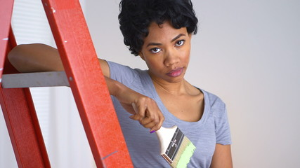 Tired African American woman with paint brush in hand