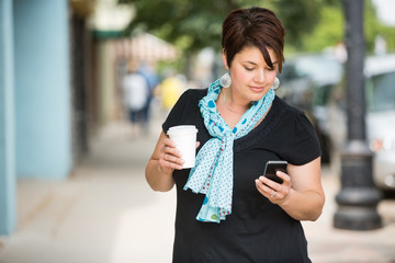 Woman Holding Coffee Cup While Messaging Through Smartphone