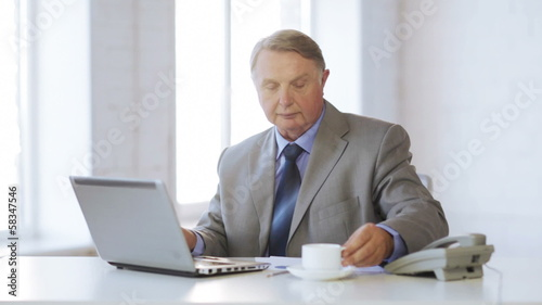 old man with laptop computer drinking coffee